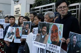 Pro-democracy activists hold pictures of Chinese activist Wu Gan (2nd-R) and other activists outside the Chinese central government's liaison office in Hong Kong, Dec. 27, 2017.