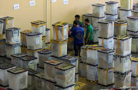 FILE - Employees of the Iraqi Independent High Electoral Commission inspect ballot boxes at a warehouse in Dohuk, Iraq, May 16, 2018.