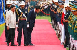 Japanese Prime Minister Shinzo Abe, third from left, escorted by Philippine President Rodrigo Duterte, left, bows to pay respects to national flags during a welcome ceremony at Malacanang Palace grounds, Jan. 12, 2017.