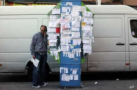 A man talks from a public phone booth covered with various personal ads including job offers, jobs wanted and rooms for rent, in Madrid, Spain, Nov. 6, 2013.