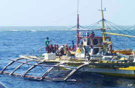 FILE - In this photo provided by Renato Etac, Chinese Coast Guard members, wearing black caps and orange life vests, approach Filipino fishermen as they confront them off Scarborough Shoal at South China Sea in northwestern Philippines, Sept. 23, 201...