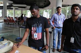 FILE - An Infosys employee sports a t-shirt featuring a U.S. flag as he buys coupons for lunch while others wait for their turn at company headquarters in Bangalore, India, April 15, 2016.