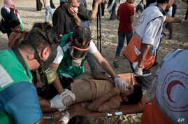 Palestinian medics evacuate a wounded youth who was shot by Israeli troops during a protest on the beach at the border with Israel near Beit Lahiya, northern Gaza Strip, Oct. 22, 2018.