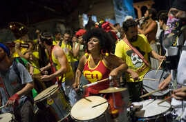 """A woman sporting a Chapulin Colorado costume, from the Mexican television series, drums during the """"Chroma Aqui na Minha Mao"""" street party in Rio de Janeiro, Brazil, Feb 8, 2018."""