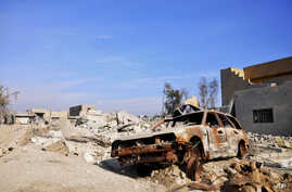A burned out car lies amid damaged buildings in Ramadi, 70 miles (115 kilometers) west of Baghdad, Iraq, on Jan. 2, 2016. Iraq's military says Islamic State militants launched suicide attacks Friday with seven suicide car bombs in two areas on the ou