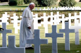 Pope Francis walks past marble crosses at the American military cemetery in Nettuno, Italy, Nov. 2, 2017.
