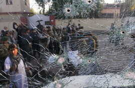 Afghan security forces are seen from a cracked side window of a vehicle, which was damaged in a suicide attack on a police headquarters in Jalalabad, Afghanistan, June 1, 2015.