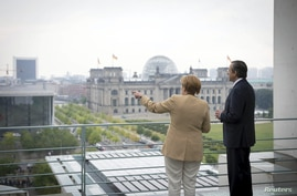 German Chancellor Angela Merkel and Greek Prime Minister Antonis Samaras (R) chat while standing on a balcony of the Chancellery, before holding a meeting in Berlin, August 24, 2012.