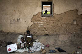 Displaced pygmies sit with their belongings outside a classroom, which serves as their shelter by night, Dec. 16, 2017 in Oicha.