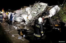 Rescue personnel survey the wreckage of TransAsia Airways flight GE222 on the island of Penghu, Taiwan, July 23, 2014.