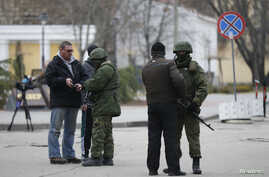 Armed men check journalists documents around the regional parliament building in the Crimean city of Simferopol March 1, 2014. U.S. President Barack Obama has warned Russia against any military intervention in Ukraine after the country's new leaders