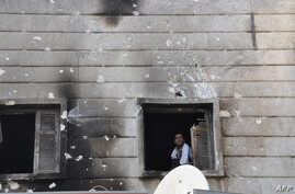Free Syrian Army fighter looks out from the window of the burnt Shaar district police station in the northern Syrian city of Aleppo after it was overrun by rebel fighters on July 25, 2012.