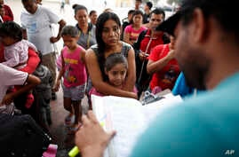 A woman from the Mexican state of Michoacan who did not give her name stands with her daughter as names are read off a list of people who will cross into the United States to begin the process of applying for asylum Thursday, July 26, 2018, near the ...