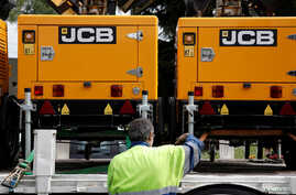 An employee loads lighting towers manufactured by JC Bamford Excavators Ltd. (JCB) at the the JCB France headquarters in Sarcelles, near Paris, France, May 22, 2017.