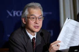 Joji Morishita, Japan's commissioner to the International Whaling Commission (IWC), holds documents as he speaks about Japan's whaling program during a press conference in Tokyo, Nov. 28, 2014.