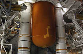 This image provided by NASA shows space shuttle Discovery with it's external fuel tank being worked on and examined in the Vehicle Assembly Building at NASA's Kennedy Space Center in Florida. NASA decided to delay the launch and allow the teams addit