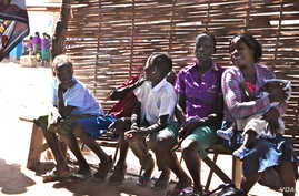 Children wait for their mothers at the Antenatal Clinic in South Sudan. (H. McNeish for VOA)