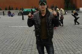 "A man identified as Tajik Alan Chekranov holding a pistol and extending one finger -- a common sign used by Islamist militants to mean ""one,"" an attestation of belief in tawhid, or monotheism -- at Red Square in Moscow, possibly in 2012."