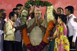 Hindu nationalist Narendra Modi, who will be the next prime minister of India, wears a garland presented to him by his supporters at a public meeting in the western Indian city of Ahmedabad, May 20, 2014