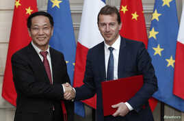 President of Airbus Commercial Aircraft, Guillaume Faury, and Chairman of China Aviation Supplies Co., Jia Baojun, shake hands during an agreement signing ceremony at the Elysee Palace in Paris, March 25, 2019.