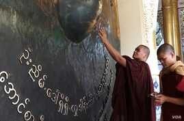 Two monks touch the large bronze gong at the Maha Muni Buddha Temple in Mandalay. (Z. Aung/VOA)