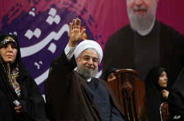 Iranian President Hassan Rouhani, center, waves to his supporters as he is accompanied by Vice President for Women and Family Affairs Shahindokht Molaverdi in a campaign rally for the May 19 presidential election in Tehran, Iran, May 9, 2017.
