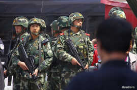Paramilitary policemen stand guard near the exit of the South Railway Station, where three people were killed and 79 wounded in a bomb and knife attack on Wednesday, in Urumqi, Xinjiang Uighur Autonomous region, May 1, 2014. A bombing in western Chin
