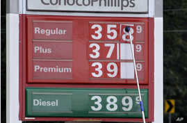 A man changes fuel prices at a ConocoPhillips gas station in Little Rock, Ark. The price of oil fell to its lowest point in nearly two months as persistent worries about the global economy overshadowed encouraging reports about U.S. consumer confiden
