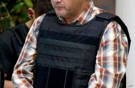 "FILE - Ivan Velazquez-Caballero, of Nuevo Laredo, Mexico, the alleged leader of the Zetas cartel in Mexico known as ""El Taliban,"" is escorted to a media presentation in Mexico City, Sept. 27, 2012."