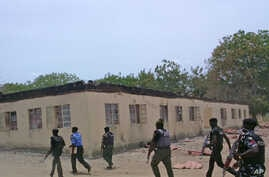 FILE - Security guards walk past a burned-out government secondary school in Chibok, Nigeria. April, 21. 2014.