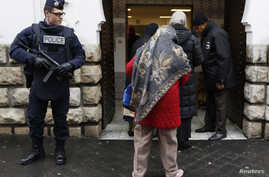 FILE - French police stand next to the entrance of Paris Mosque as French Muslims arrive for Friday prayers in Paris.