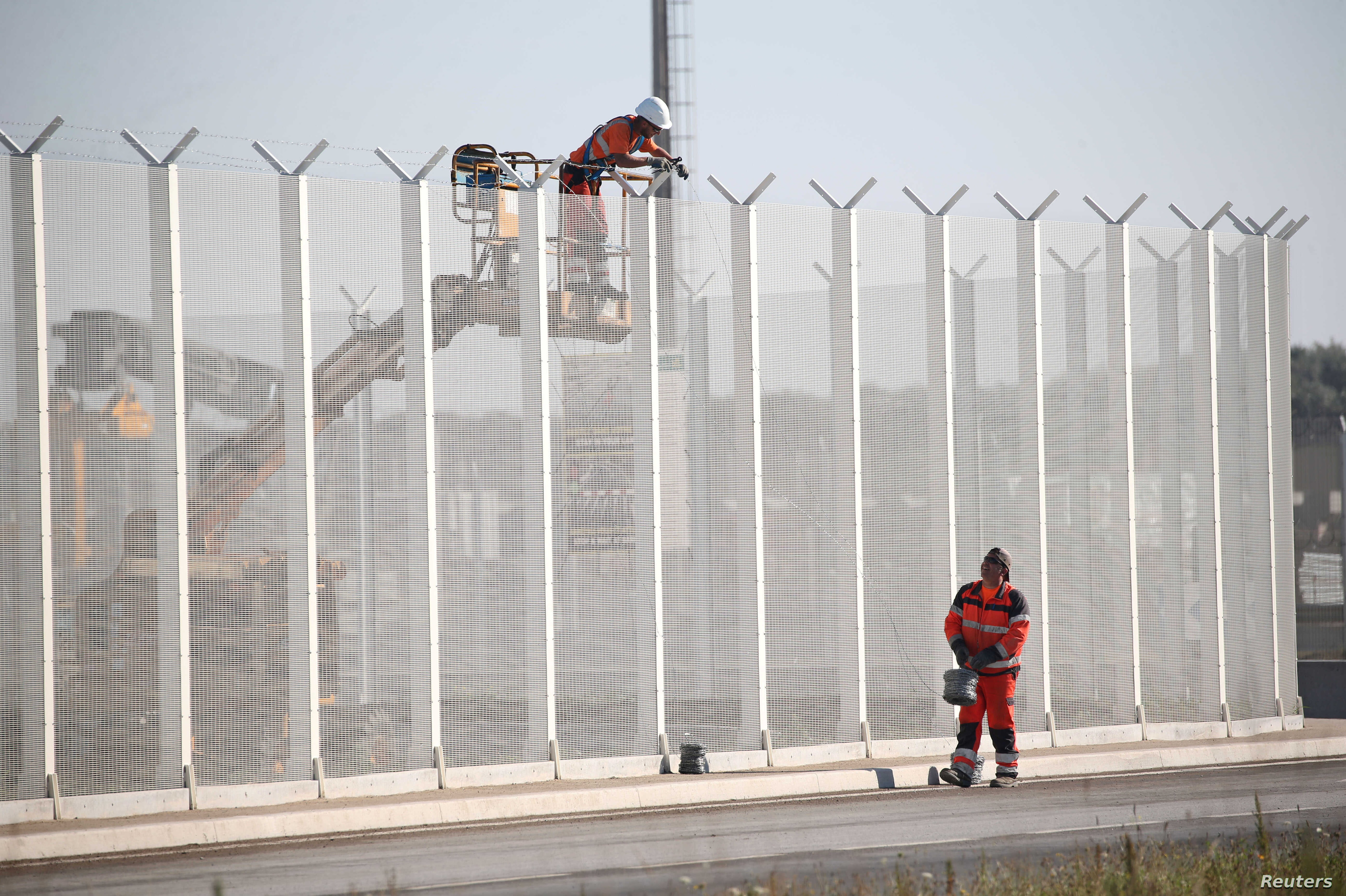 Workers set-up barbed wires on top of a fence along the harbour of Calais to prevent migrants jumping aboard lorries, France, Sept. 7, 2016.