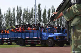 Criminals and suspects are transported to a stadium for a mass sentencing rally in Yili, Xinjiang Uighur Autonomous Region May 27, 2014. Local officials in China's western Xinjiang region held the public rally for the mass sentencing of criminals on