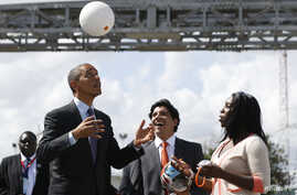 "FILE - U.S. President Barack Obama bounces a soccer ball with his head at Ubungo Power Plant in Dar es Salaam, July 2, 2013. The ball, called a ""soccket ball,"" has internal electronics that allow it to generate and store electricity that can power sm"