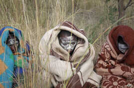 Xhosa boys covered with a blankets and smeared with chalky mud sit in a field as others undergo a traditional male circumcision ceremony into manhood near the home of former South African president Nelson Mandela in Qunu, South Africa, June 30, 2013.