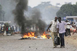 Two men carry a suitcase past a burning barricade in Bujumbura, Burundi, April 30, 2015, after the government issued and ordered for all university campuses to close down.