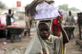 A girl sells drinking water packed in small plastic bags on a street in the northern city of Maiduguri, Nigeria, August 2009.