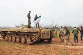 Rebel fighters walk past an armored vehicle carrying the flag of the Tahrir al-Sham rebel alliance near the town of Maardes in the countryside of the central Syrian province of Hama, March 22, 2017. Tahrir al-Sham has recently emerged as the most pow