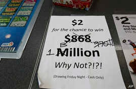An updated paper sign is displayed the counter of a 7-Eleven store shows that the Mega Millions estimated jackpot has soared to $1 billion Oct. 19, 2018, in Chicago. No one won Friday, and the jackpot is estimated to be $1.6 billion by Tuesday's draw