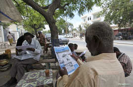 FILE - People read newspapers in the streets of Somalia's capital Mogadishu May 3, 2011.