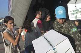 Laura Cartanya, left, representing the Spanish Agency for International Development Cooperation (AECI), supervises the unloading of humanitarian aid items for Haiti's fight against cholera at the international airport in Port-au-Prince, 27 Oct 2010