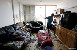 An Israeli surveys the damage to his apartment after a rocket, fired from Gaza, struck a nearby house in the southern coastal city of Ashkelon, August 26, 2014.
