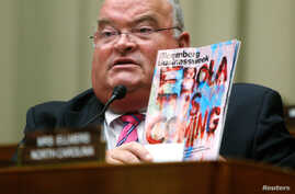 U.S. Representative Billy Long holds up a magazine with an Ebola headline at a House Energy and Commerce Oversight and Investigations Subcommittee hearing.