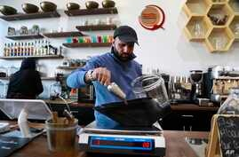 In this Jan. 9, 2018, photo, Ibrahim Alhasbani, owner of Qahwah House, a cafe that serves coffee made from beans harvested on his family's farm in Yemen's mountains, measures coffee beans in Dearborn, Mich.