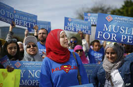 """Protesters stand across the street from a Donald Trump rally holding signs for """"Muslims for Peace,"""" signs before a campaign rally in Orlando, Fla."""