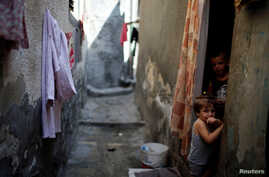 Palestinian children look out of their homes at Al-Shati refugee camp in Gaza City, Sept. 3, 2018.