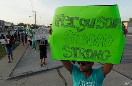 People march about a mile to the police station to protest the shooting of Michael Brown, Aug. 20, 2014, in Ferguson, Mo.