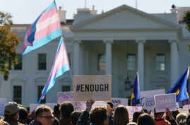 FILE - Members of the Human Rights Campaign and other LGBTQ activists gather on Pennsylvania Avenue in front of the White House in Washington, Oct. 22, 2018.