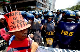 Riot police block protesters as they try to march towards U.S. Embassy in Manila to mark International Labor Day, May 1, 2013 in Manila, Philippines.
