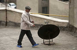 An Iranian man walks past a satellite dish on a rooftop in northern Tehran, January 15, 2011.